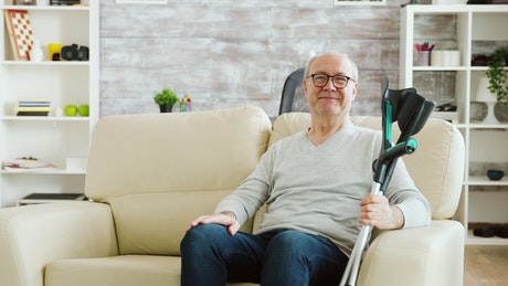 Smiling elderly man holding crutches and sitting on sofa
