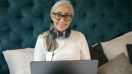 Smiling elderly woman on laptop in bed