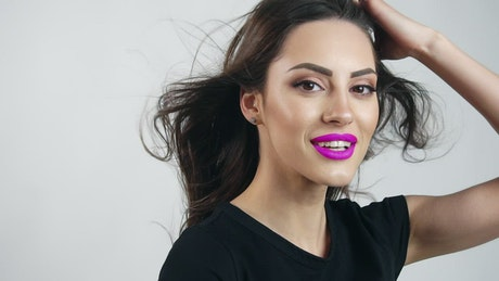 Smiling model in purple lipstick on white background