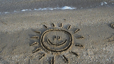 Smiling sun drawn in the sand on a beach