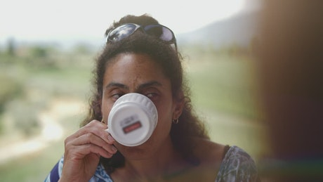 Smiling woman sips coffee and listens to companions