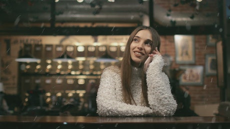Smiling woman watches snowfall while on mobile in cafe