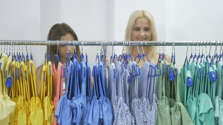 Smiling women promote kid's clothing sale
