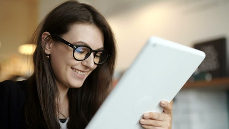 Smiling young woman surfs internet on tablet