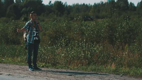 Smoking man hitchhiking in a rural area