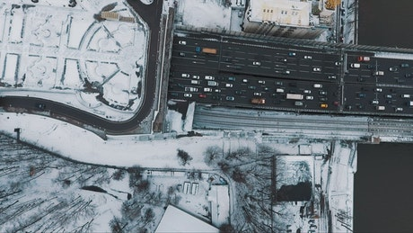Snow covered buildings by a large road