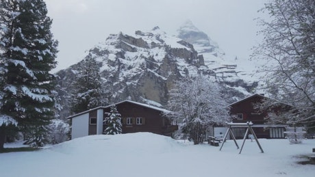 Snow covered cabins at base of a mountain