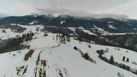 Snow-covered hill in a mountain range, aerial shot
