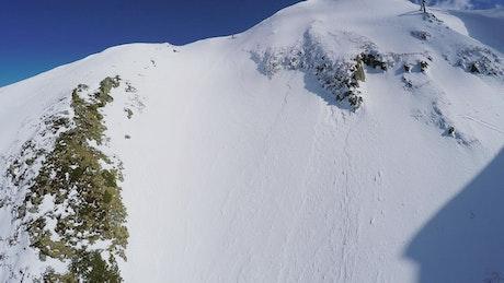 Snowboarder heading down a steep mountain
