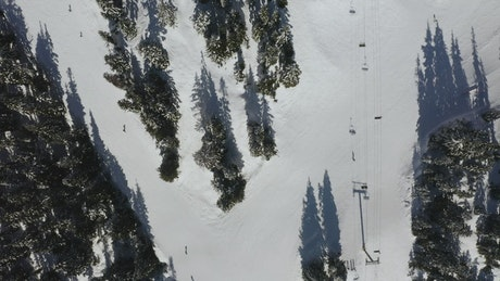 Snowy hill with skiers from above