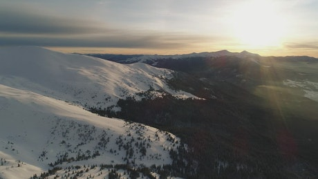 Snowy top of mountains at sunset, aerial shot