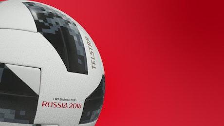 Soccer football ball spinning on red