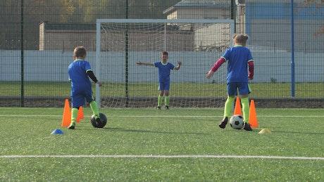 Soccer players training against a Goalie