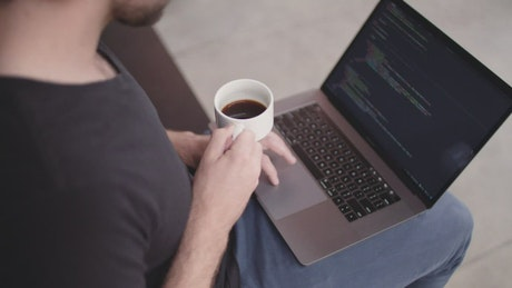 Software developer holding a coffee cup