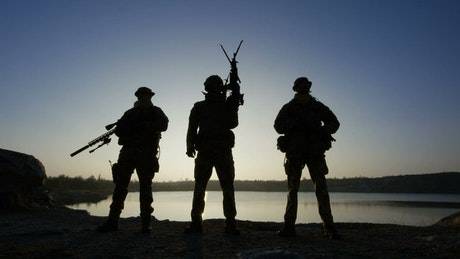 Soldier silhouettes posing with guns in the sunset
