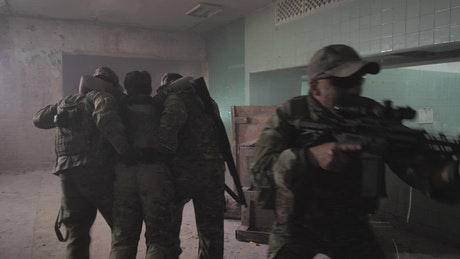 Soldiers carrying a wounded man through a building