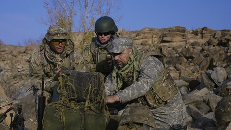 Soldiers looking at computer outdoors