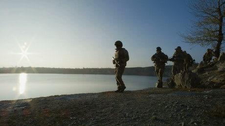 Soldiers walking by the lake at sunset