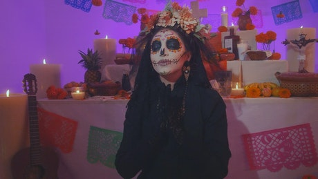 Solemn catrina praying at the foot of an altar of the dead