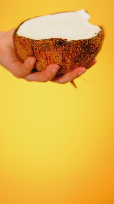 Spilling water from a coconut on a yellow background