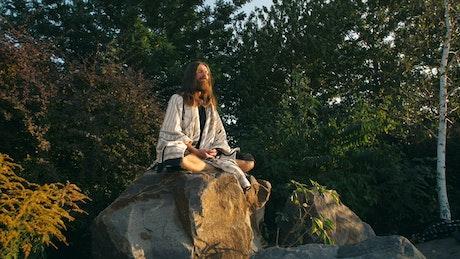 Spiritual man meditating on a rock in nature