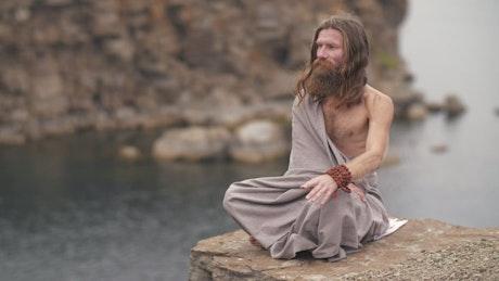 Spiritual man meditating on the shore of a lake
