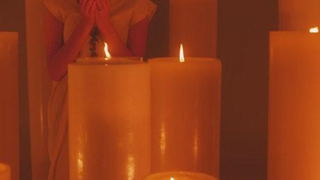 Spiritual woman meditating among many candles