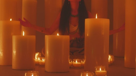 Spiritual woman meditating surrounded by many candles