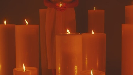 Spiritual woman surrounded by lots of candles