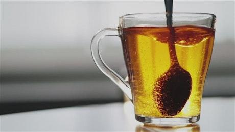 Spoon stirring sugar in clear glass tea cup