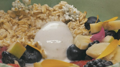 Spoon taking a mix of yougurt with seasonal fruits
