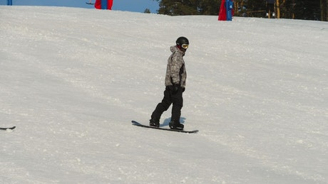 Sportsman snowboarding down the hill