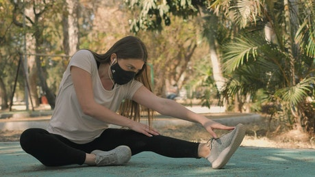 Sportswoman stretching with a face mask