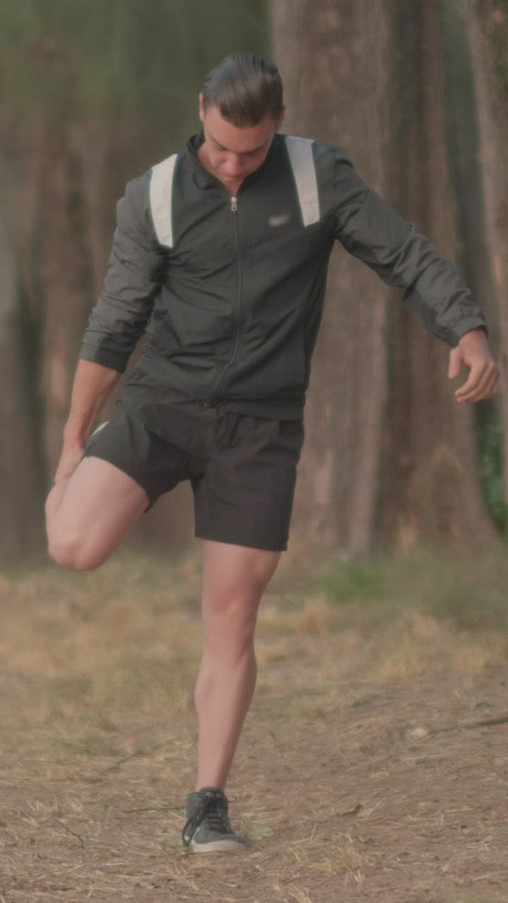 Sporty man stretching in the middle of a forest
