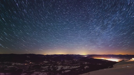 Starry sky during sunrise in the mountains