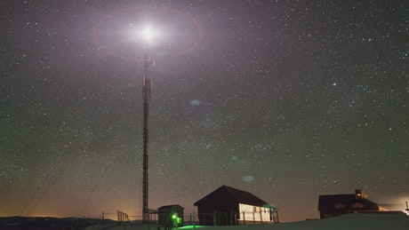 Starry sky on a place with a communications tower
