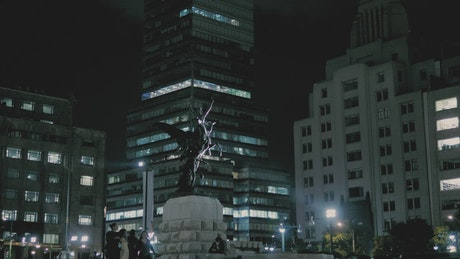 Statue in a city square downtown at night
