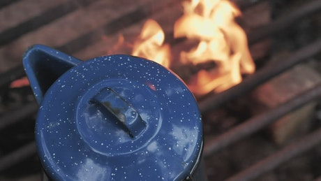 Steel kettle on a campfire with flames