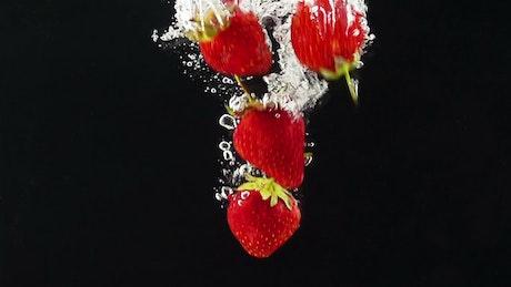 Strawberries falling through water