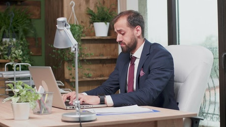 Stressed man in suit yawns and types on laptop
