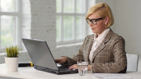 Stressed woman treats headache while working on laptop