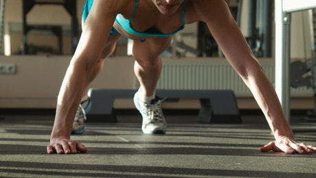 Strong woman doing push-ups, ground view