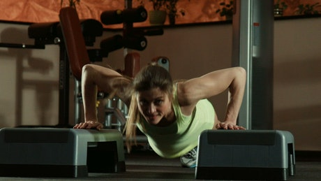 Strong woman doing push-ups in the gym