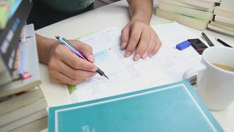 Student doing homework on a desk with many books