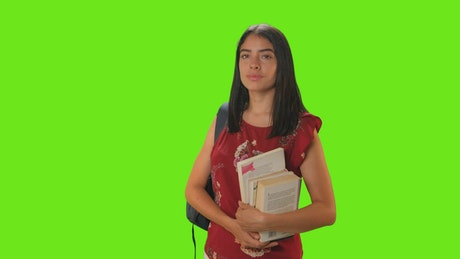 Student girl from the front smiling on a green background