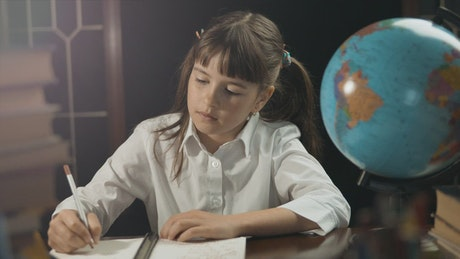 Student girl poses next to a globe