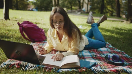 Student learning in park with laptop and book