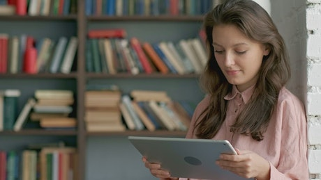 Student reading on a tablet at a library