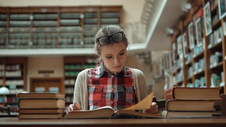 Student stressed over exam sits with books in library