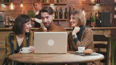 Stylish friends share ideas at hip cafe with laptop